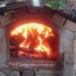 ~パン釜に薪を入れて温め中~